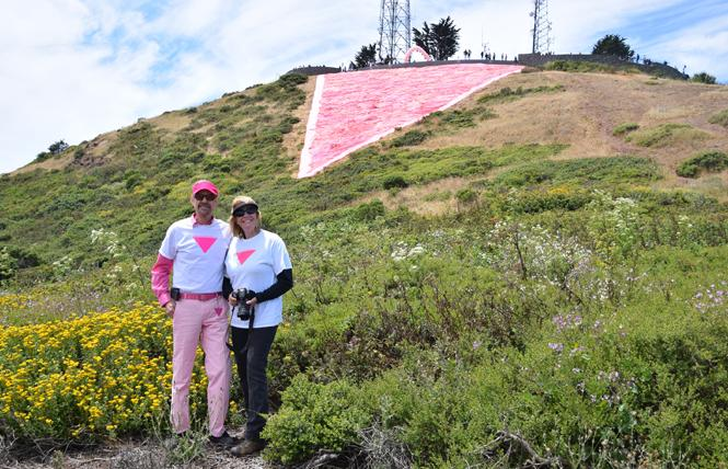 Patrick Carney, left, and his sister, Colleen Hodgkins, stand near the completed pink triangle June 29. Photo: Hossein Carney