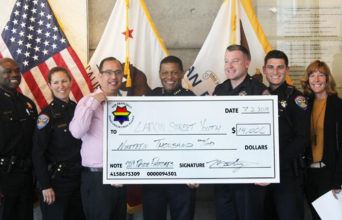 San Francisco Police Chief William Scott, center, joined Larkin Street Youth Services Executive Director Sherilyn Adams, at right, and other officers to present the check from Pride patch sales. Photo: Courtesy SFPD
