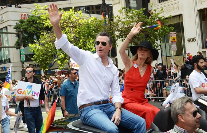 Governor Gavin Newsom, shown riding in the San Francisco Pride parade with his wife, Jennifer Siebel Newsom, included funding in his state budget for LBQ women's health. Photo: Rick Gerharter