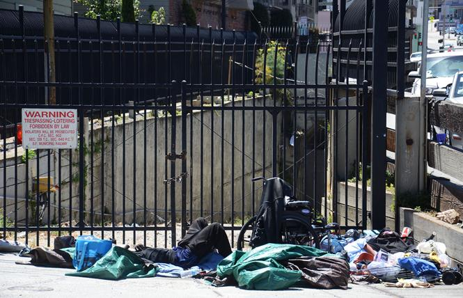 A man slept on Market Street near Collingwood Street last month. Photo: Rick Gerharter