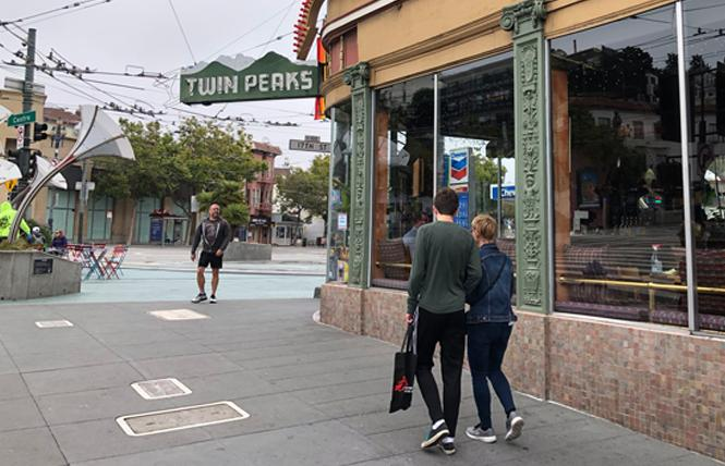 People walk past the Twin Peaks Tavern on a recent morning. Photo: Matthew S. Bajko