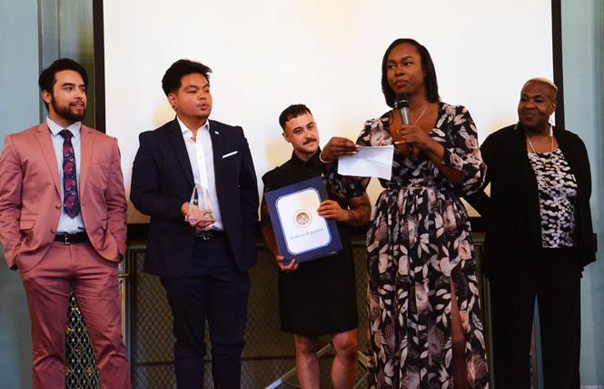 Akira Jackson accepts the Bill Kraus Leadership Award on behalf of the Our Trans Home SF coalition during the Harvey Milk LGBTQ Democratic Club annual dinner Monday, July 29. Other members of the coalition joined Jackson on stage. Photo: Rick Gerharter