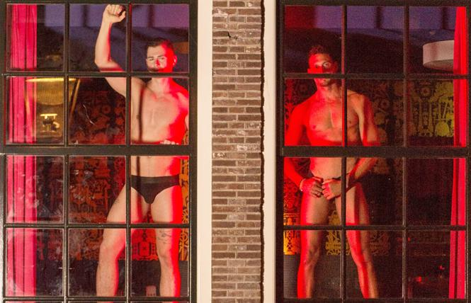 Escort model Lukas Daken, left, dances with a fellow HUNQZ escort model, right, to raise awareness of sex worker's labor rights in the My Red Light window in Amsterdam's red-light district during Amsterdam Pride August 3. Photo: www.keefwilliams.com