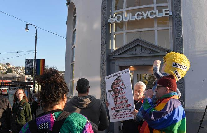 "Activist Michael Petrelis, right, held an ""Impeach Trump"" piñata during his protest Wednesday outside SoulCycle in the Castro. Photo: Bill Wilson"