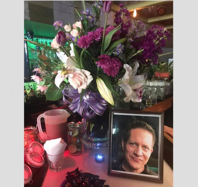 A floral arrangement next to a photo of Frank Schumacher.