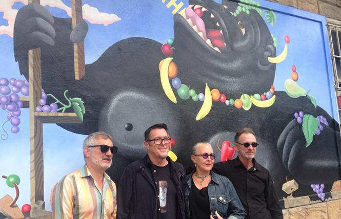 "Peter Toscani, left, Donald Harvey, Meredith Clark, and Michael Ritter stand in front of the restored ""Laughing Gorilla"" mural during the August 10 unveiling. Photo: Veronica Dolginko"