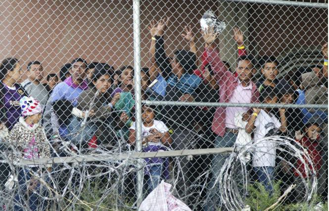 In this March 27, file photo, Central American migrants wait for food in a pen erected by U.S. Customs and Border Protection in El Paso, Texas. Photo: Courtesy AP
