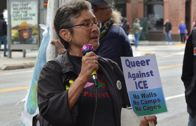 QUIT organizer Carla Schick speaks in front of Immigration and Customs Enforcement's San Francisco office Monday during the Queers Melt ICE rally. Photo: Samantha Laurey