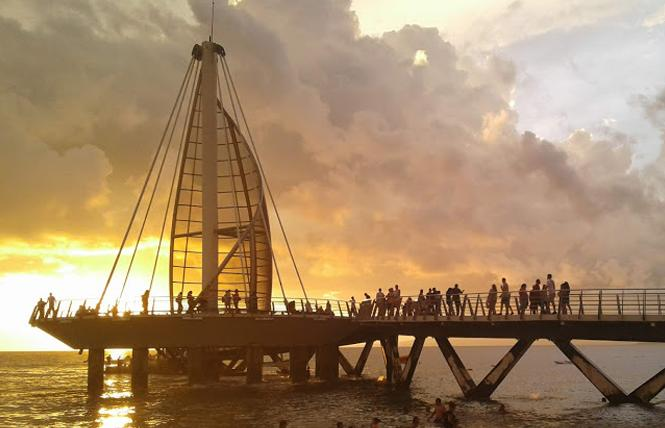 Visitors are drawn to sunset at the pier on Los Muertos Beach. Photo: Ed Walsh