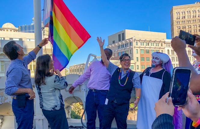 Oakland Mayor Libby Schaaf, second from left, raises the Pride flag at Oakland City Hall Tuesday as out Councilwoman Rebecca Kaplan raises her hand. Photo: Jane Philomen Cleland