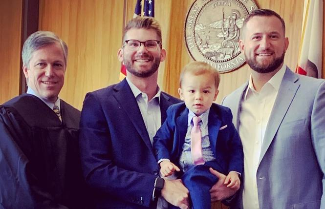 Sacramento City Councilman Steve Hansen, right, and his partner, Michael McNulty, hold their son, Henry, after the judge finalized the adoption. Photo: Courtesy Facebook