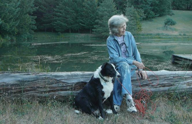 "Sally Gearhart sits by a lake with her dog, Bodhi, in a scene from the film, ""A Great Ride."" Photo: Courtesy Deborah Craig"
