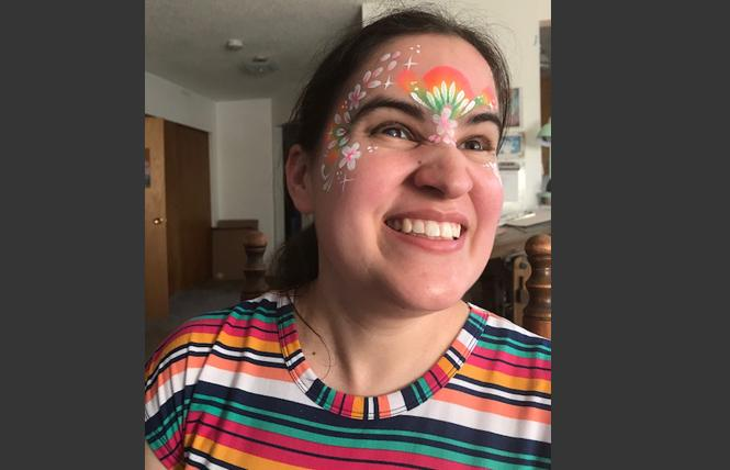 Caitlin Hernandez is beaming as she wears rainbow face paint with stars, dots, and flower petals. Photo: Jack Sanders/Face paint: Haley Brown, www.haleybrown.org.