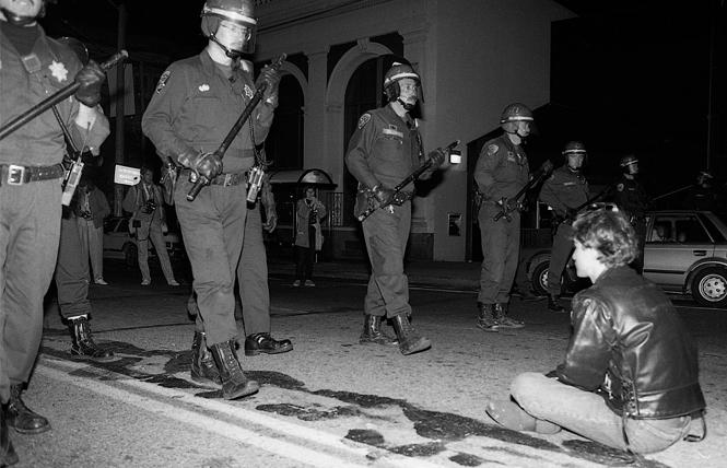 A single activist sits down in the middle of Castro Street as San Francisco police march in riot formation down the street on October 6, 1989. Photo: Rick Gerharter