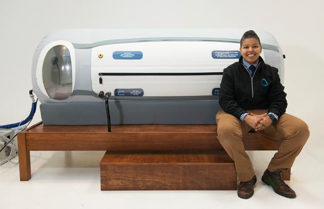 Alex Williams sits by a hyperbaric chamber; she recently opened a larger spa in Oakland. Photo: Courtesy Alex Williams