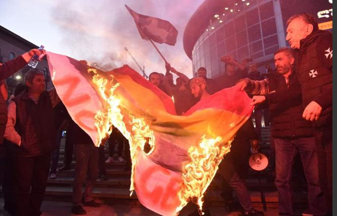 "Anti-gay demonstrators burn a rainbow flag before the Tbilisi premiere of ""And Then We Danced"" on November 8. Photo: Courtesy RFE/RL"