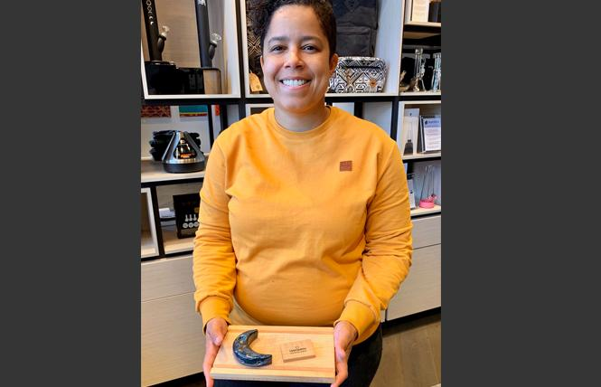 Marcella Sanchez holds a one-of-a-kind moon pipe by Wandering Bud on a custom limited edition rolling tray made by local woodworker Oaksmith, which includes a joint holder. Photo: Sari Staver