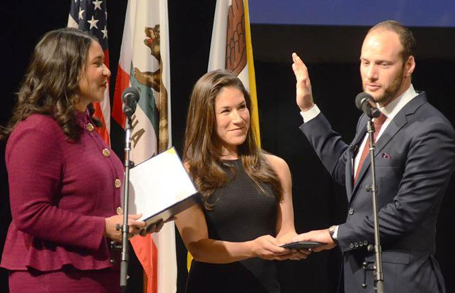 Mayor London Breed, left, administers the oath of office January 8 to District Attorney Chesa Boudin, who was joined on stage by his wife, Valerie Block. Photo: Rick Gerharter