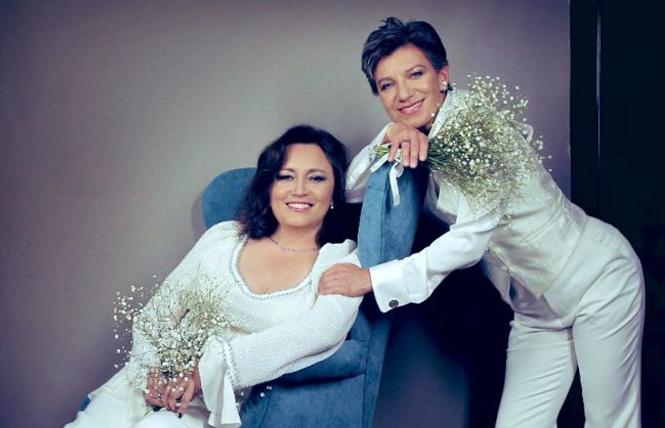 Angel Yanez, sitting in a chair, posed with her wife, Bogota Mayor Claudia López, in a wedding photo the couple released. Photo Credit: Raúl Higuera/Claudia López/Twitter