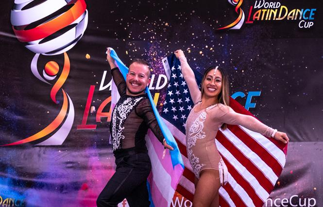 Luis Gutierrez-Mock, left, holding the trans pride flag, and Ngoc Huynh, won the amateur bachata cabaret division at the World Latin Dance Cup in Medellin, Colombia in December. Photo: Takeshi Young/World Latin Dance Cup