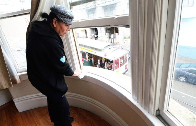 Jane Cordova cleans the windowsill in her new room at the Trans Home SF apartment, which overlooks the cable car route. Photo: Rick Gerharter