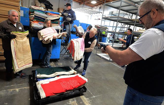 Bob Lenzi, right, keeps track as volunteers Larry Wolfson, left, Beth Feingold, Matt Polsdorf, and Holly Branscombe unload AIDS Memorial Quilt panels before stacking on shelving at a San Leandro warehouse February 14. Photo: Rick Gerharter
