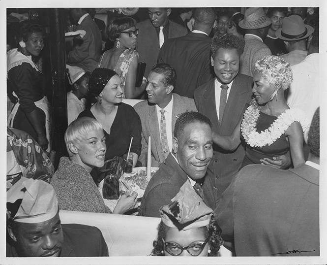 "Leola King (seated in black hat) with Lottie ""The Body"" Claibourne (standing with lei) and unknown female impersonator referred to by Frank Jackson at Harlem of the West website (with arm around Lottie) at the Texas Playhouse on September 10, 1958. credit: Wesley Johnson III Collection"