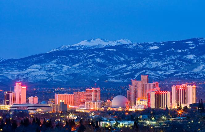 Downtown Reno is lit up at night with the snowcapped Sierra Nevada Mountains in the background. Photo: Andy/Adobe Stock