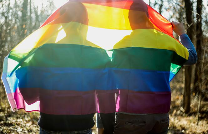 A gay couple walks through the woods draped with a rainbow flag. Photo: Courtesy Human Rights Campaign
