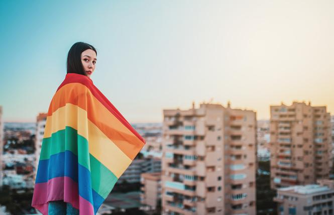 An Asian woman wrapped in a rainbow flag overlooks a city. Photo: Dark Saiyaman/Adobe Stock