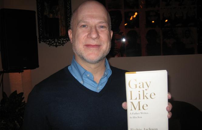 "Richie Jackson holds a copy of his memoir, ""Gay Like Me: A Father Writes to His Son,"" at his February event at Manny's in San Francisco. Photo: Brian Bromberger"