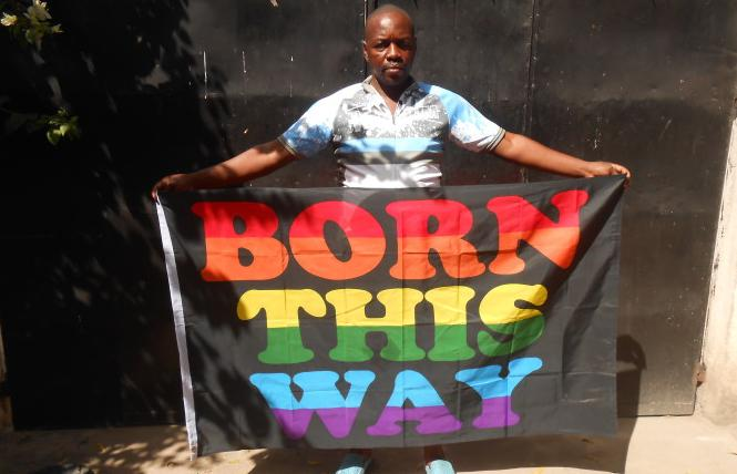 "A Tanzanian holds up a ""Born This Way"" banner. Photo Credit: Courtesy LGBT Voice"