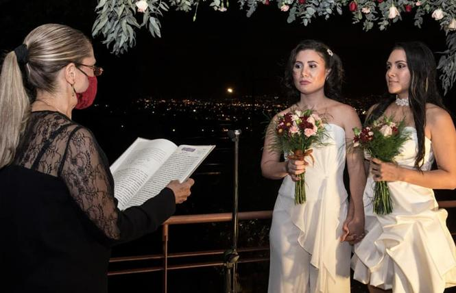 Alexandra Quiros Castillo, center, and Daritza Araya Arguedas, right, stand before notary Ana Cecilia Castro Calzada during their wedding in Heredia, Costa Rica, on May 26. Photo: Ezequiel Becerra/AFP