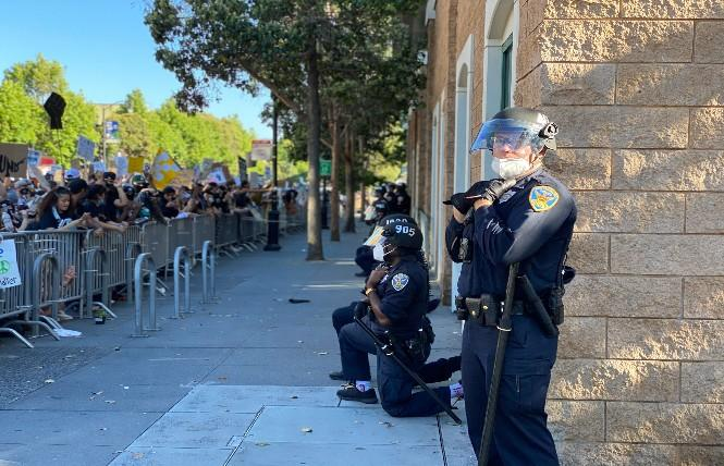 Outside Mission Station, some San Francisco Police officers take a knee, while one does not, during Wednesday's protest against the police killing of George Floyd in Minneapolis. Photo: John Ferrannini