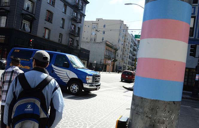 There will be a march for trans rights Thursday in the Tenderloin, which has light poles painted in the colors of the trans flags. Photo: Rick Gerharter