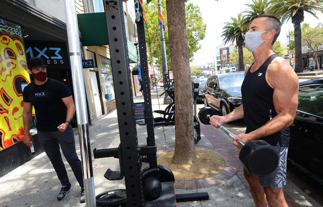 MX3 Fitness co-owner Glenn Shope, left, directs Shayne Jones through his outdoor workout on the Market Street sidewalk outside the business due to COVID-19 restrictions. Photo: Rick Gerharter