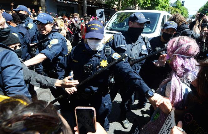 Police officers became aggressive and highly provocative when marchers surrounded their unmarked van during the Pride is a riot march Sunday, June 28. Photo: Rick Gerharter