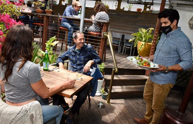 Ramsey Garcia, right, co-owner of Fable, serves Katie Brillault and Rick Holthouse on the patio of the restaurant. Photo: Steven Underhill