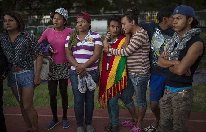 LGBTQ migrants stand on the racetrack at the Jesus Martinez stadium, which was turned into a makeshift shelter for the migrant caravan in Mexico City in 2018. Photo Credit: Courtesy Rodrigo Abd/Associated Press