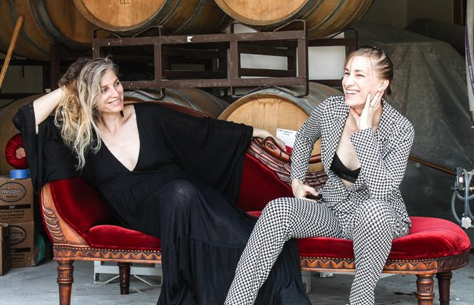 Morgan Murphy, left, and her spouse, Maggie Przybylski, sit in front of fermenting equipment and barrels of their cider at Two Broads Cider in San Luis Obispo. Photo: Courtesy Two Broads Cider
