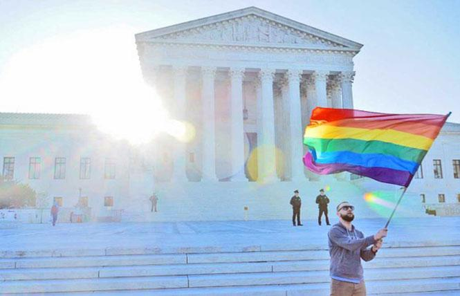 A person waves a rainbow flag outside of the U.S. Supreme Court. Photo: Scott Drake