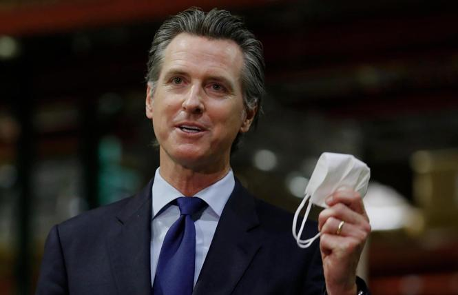 Governor Gavin Newsom held a face mask as he urged people to wear them to fight the spread of the coronavirus during a June news conference in Rancho Cordova, California. Photo: AP/Rich Pedroncelli, Pool