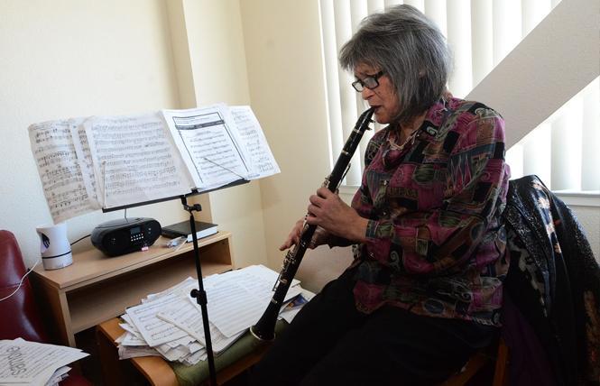 Jasmine Gee plays her clarinet in her apartment. Photo: Rick Gerharter