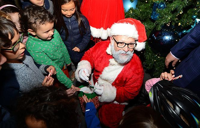 Santa stopped by the annual lighting of the Castro Merchants' holiday tree in 2018 to pass out candy canes to the children who were there. Photo: Rick Gerharter