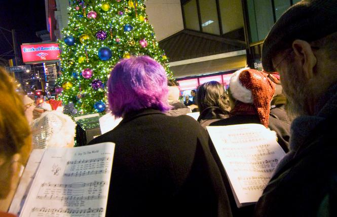 Carolers, joined by the San Francisco Lesbian/Gay Freedom Band, heralded the lighting of the annual Castro holiday tree in 2012. Photo: Rick Gerharter