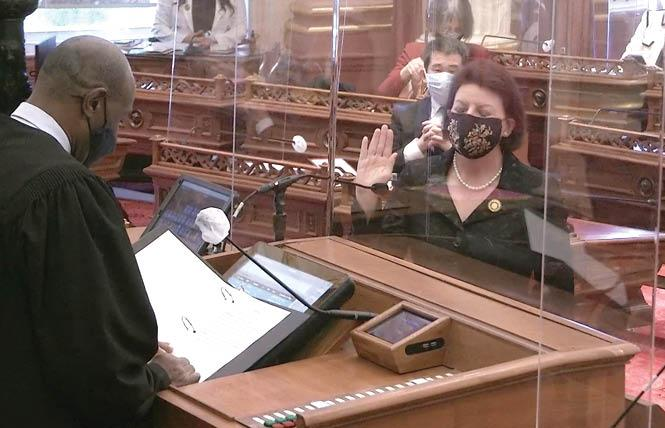 California Supreme Court Justice Martin Jenkins, left, swears in state Senator Toni Atkins Monday, December 7, at the Capitol in Sacramento. Atkins' colleagues also reelected her as the chamber's leader. Photo: Courtesy Screengrab
