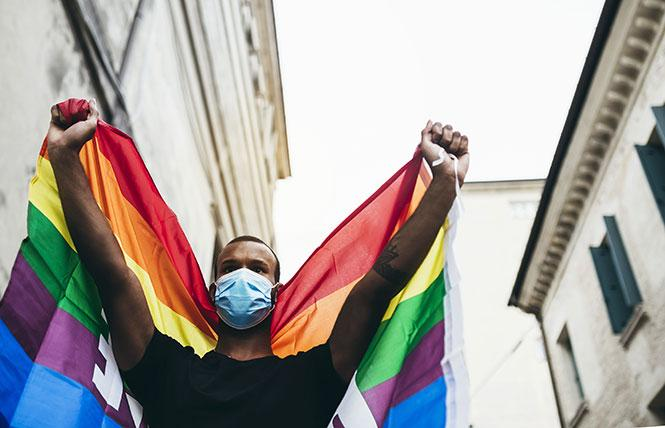 A masked demonstrator holds up a rainbow flag. Photo: AdobeStock
