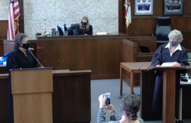 Alameda County Superior Court Judge Elena Condes, left, was sworn in by retired Judge Cecilia Castellanos, right, as Condes' spouse, Danielle, records the proceedings and Presiding Judge Tara Desautels looks on. Photo: Screengrab via BlueJeans.