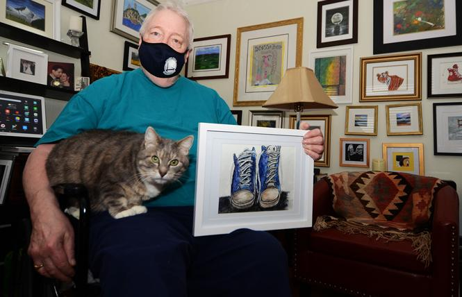 Brian Lynch sits with his cat, Lil Guy, and holds one of his favorite paintings. His other works are on the two walls behind him. Photo: Rick Gerharter
