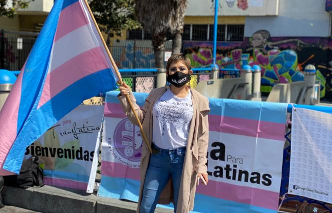 Victoria Castro holds a trans flag as she speaks at a March 19 rally in San Francisco calling for trans people in federal immigration custody to be released. Photo: John Ferrannini